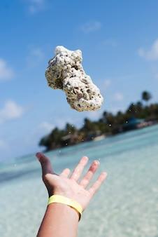 Mão jogando pedra à beira-mar