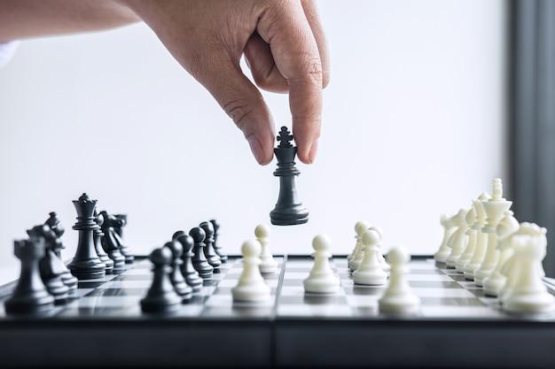 Mão jogando xadrez com peões preto e brancos