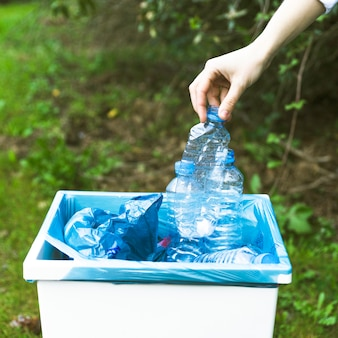 Mão, jogar, garrafa plástica, em, caixa
