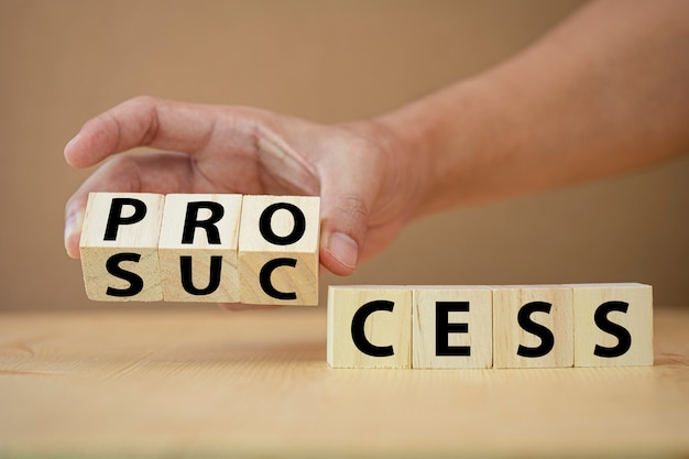 Mão lançando cubos de madeira para alterar a redação do processo para o sucesso