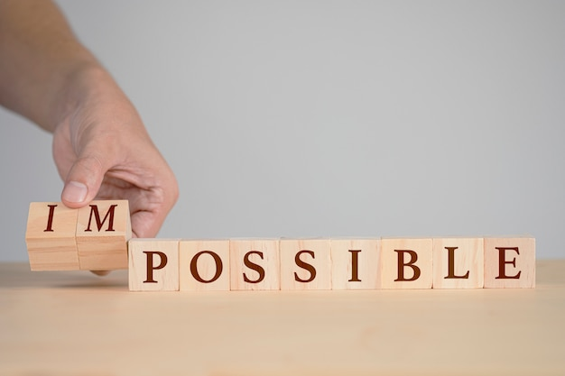 Mão lançando cubos de madeira para alterar a redação entre impossível e possível.