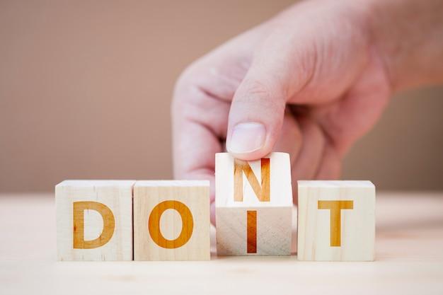 Mão lançando cubos de madeira para alterar as palavras entre não fazê-lo.