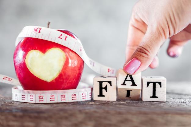 Mão lançando gordura para caber palavra com maçã vermelha e fita métrica