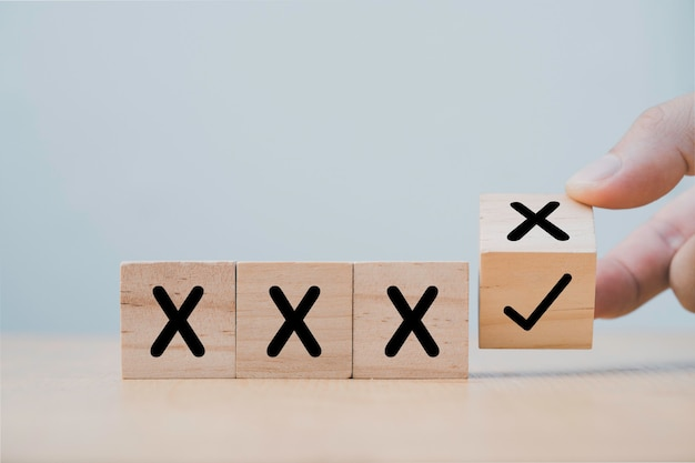 Mão lançando o bloco de cubo de madeira para mudar a cruz incorreta para a marca correta.