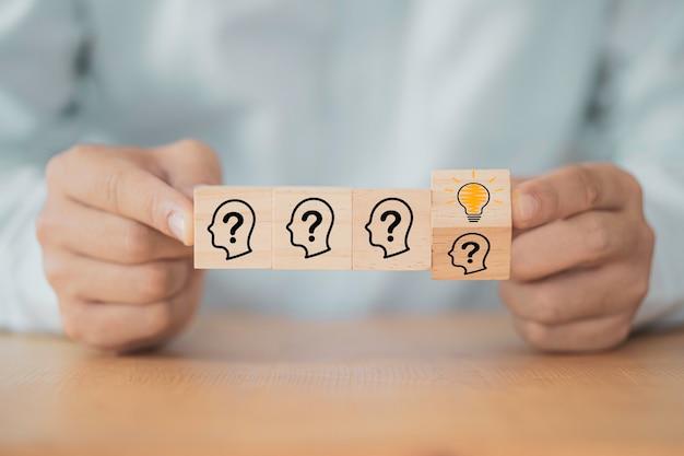 Mão lançando o bloco de cubo de madeira que imprime a face da tela com ponto de interrogação para lâmpada, ideia criativa e conceito de inovação.