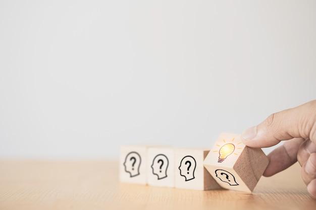 Mão lançando um bloco de cubo de madeira que imprime a face da tela com o ponto de interrogação na lâmpada