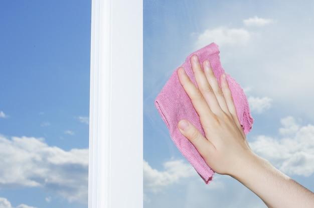 Mão lavar uma janela com um pano