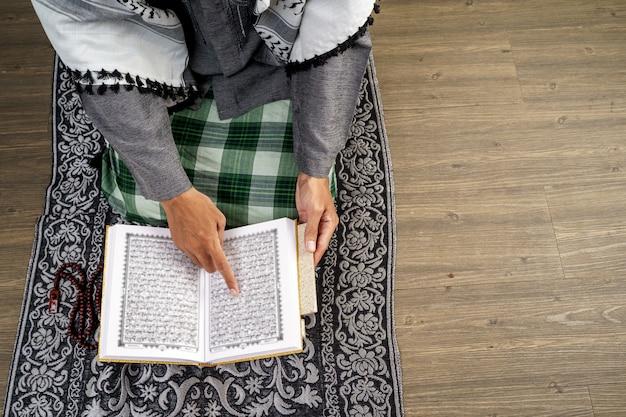 Mão lendo o alcorão e orando