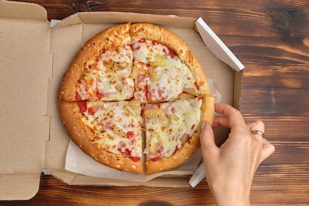 Mão leva um pedaço de pizza havaiana de embalagens de papelão