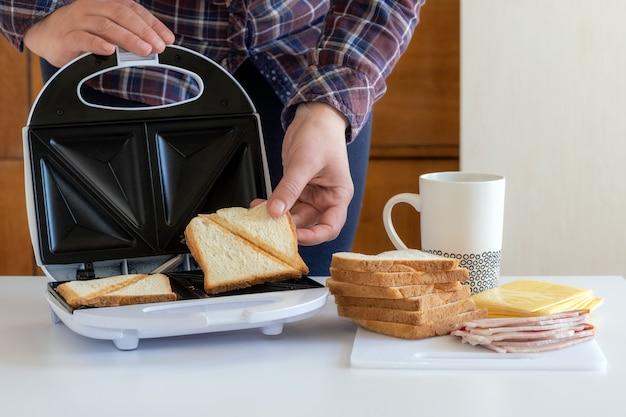 Mão leva uma fatia de pão frita perto da toster para sanduíches com queijo, bacon e café na mesa.