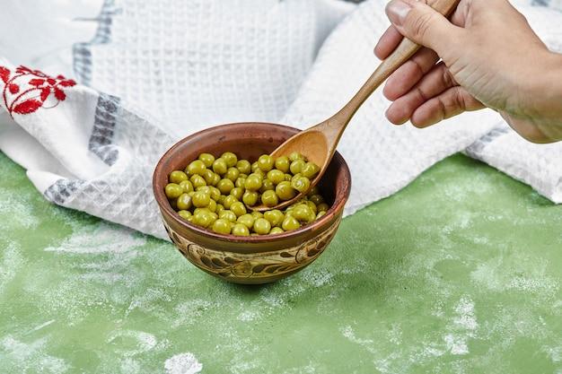 Mão levando uma colher de ervilhas cozidas sobre uma mesa verde.