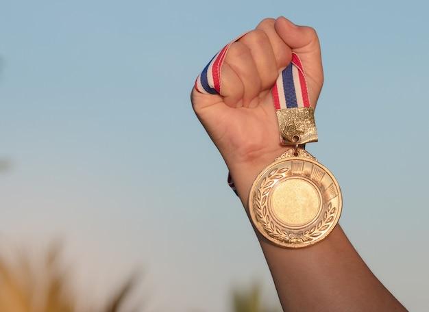 Mão levantada e segurando a medalha de ouro contra o céu. conceito de prêmio
