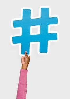 Mão levantada segurando o ícone de hashtag