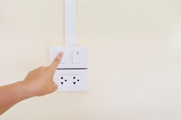 Mão ligando ou desligando o interruptor de luz