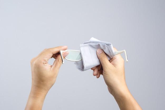 Mão limpando as lentes dos óculos de visão