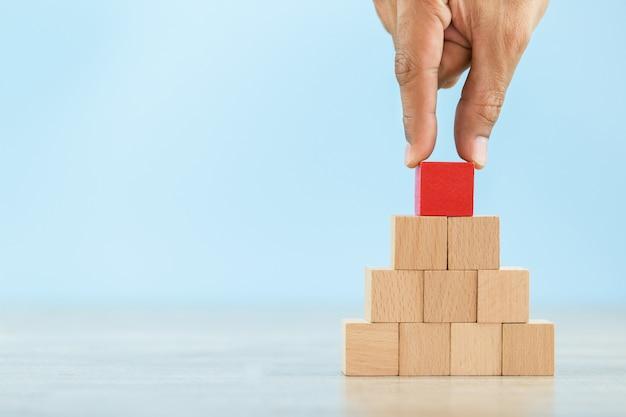 Mão mais perto mãos de empresários, empilhando blocos de madeira em etapas, conceito de sucesso do crescimento do negócio