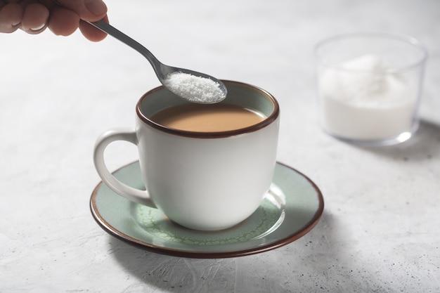 Mão masculina adoçante de café com adoçante estévia