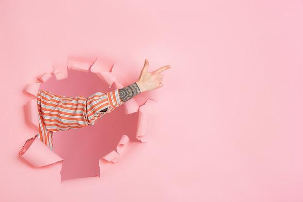 Mão masculina apontando mostrando em um buraco de papel coral rasgado na parede do copyspace