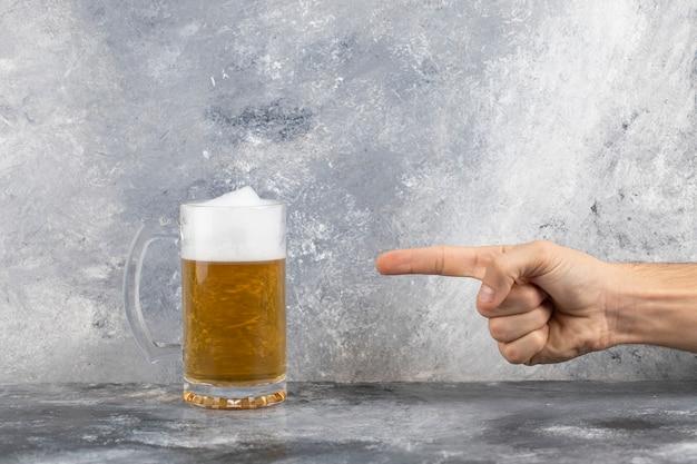 Mão masculina apontando para uma caneca de vidro de cerveja colocada em uma superfície de pedra
