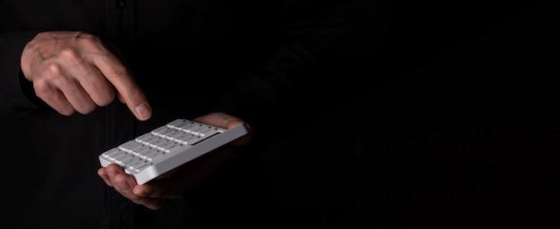 Mão masculina, calculando impostos e orçamento ou investindo riscos na calculadora branca sobre fundo preto com espaço de cópia para o texto.
