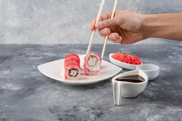 Mão masculina colhendo rolo de sushi com pauzinhos no fundo de mármore