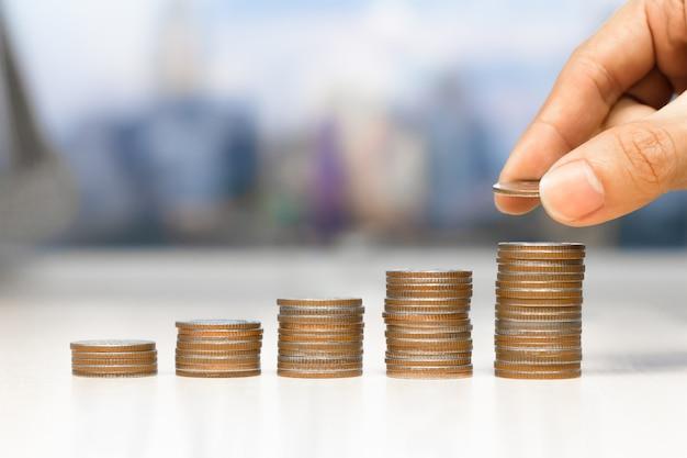 Mão masculina, colocando dinheiro moeda pilha crescente negócio