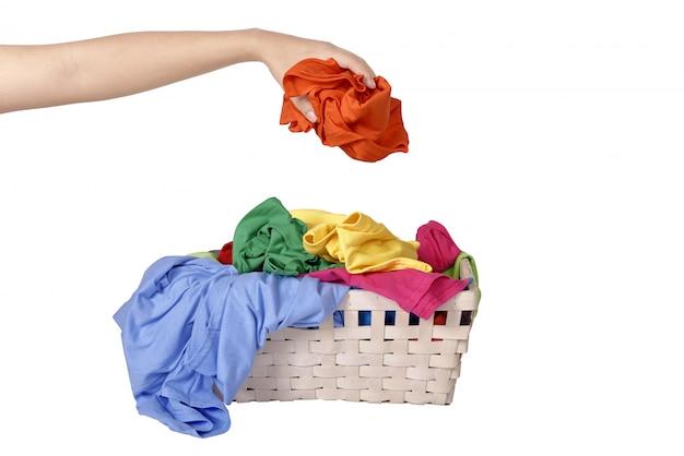 Mão masculina colocar a roupa suja na cesta