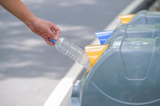 Mão masculina colocar garrafa usada na lixeira