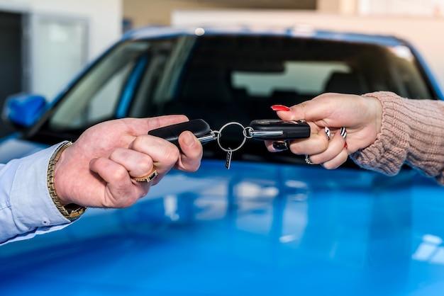 Mão masculina com as chaves do carro contra carro novo no showroom