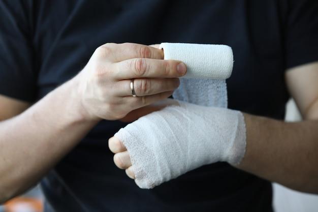 Mão masculina com bandagem elástica apertada no braço closeup