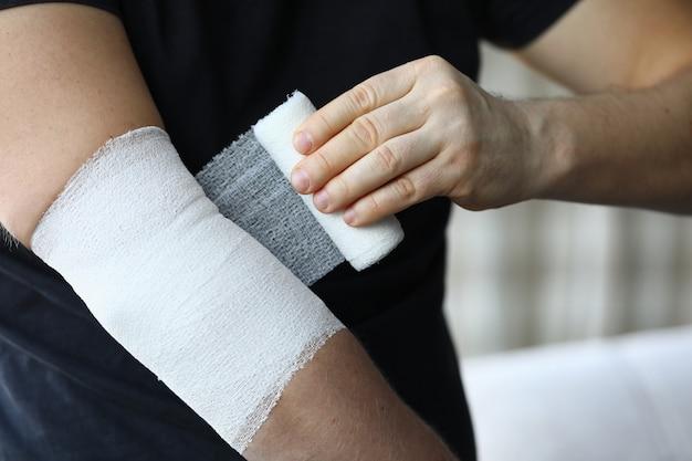 Mão masculina com bandagem elástica apertada no cotovelo closeup