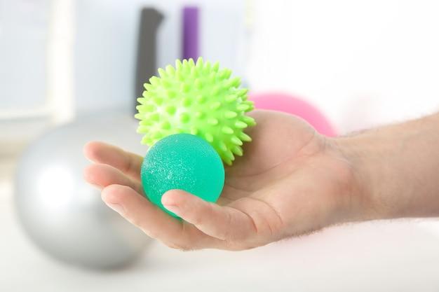 Mão masculina com bolas de estresse na clínica