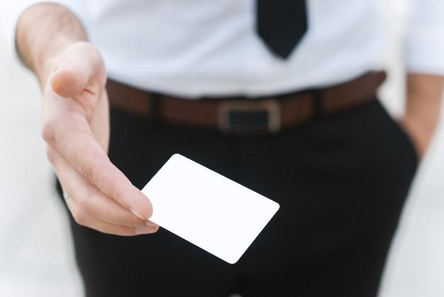 Mão masculina com cartão vazio branco, foto de close-up com foco seletivo