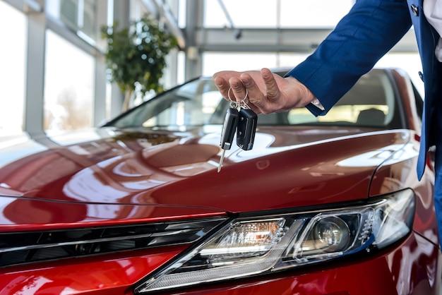 Mão masculina com chaves contra novo carro vermelho