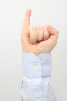 Mão masculina com dedo mínimo levantado em um fundo branco
