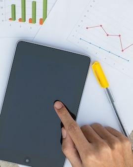 Mão masculina com gráfico de documentos de negócios com tablet digital