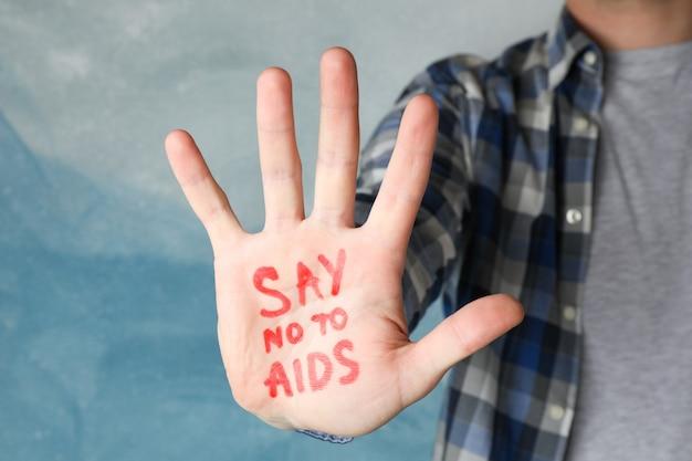 Mão masculina com inscrição diga não à aids na parede azul, espaço para texto