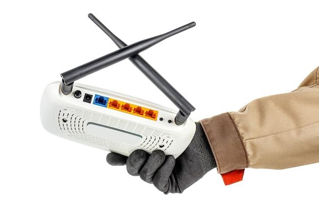 Mão masculina com luva protetora preta e uniforme marrom segurando um roteador wi-fi sem fio em branco