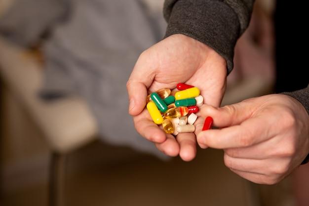 Mão masculina com multivitaminas e suplementos diários para uma vida saudável