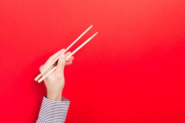 Mão masculina com pauzinhos no vermelho. comida asiática tradicional com emty