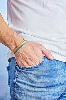 Mão masculina com pulseira de arco-íris e orgulho de texto no bolso da calça jeans