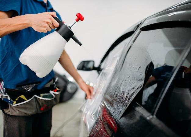 Mão masculina com spray, instalação de pintura na janela do carro