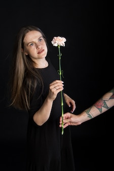 Mão masculina com tatuagens dá flor de cravo para uma linda menina morena com cabelo comprido, conceito de parabéns sobre fundo preto