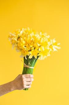 Mão masculina com um buquê de flores