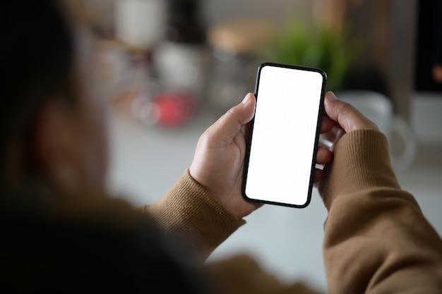 Mão masculina com um celular preto com tela branca em branco