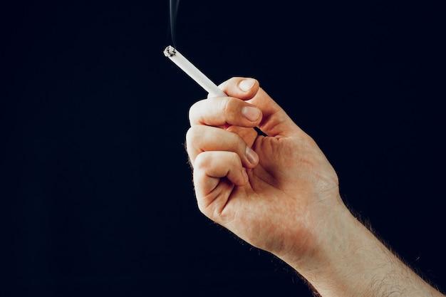 Mão masculina com um cigarro aceso contra um fundo preto