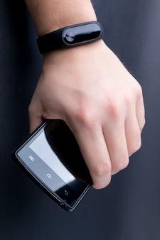 Mão masculina com um rastreador de fitness e smartphone