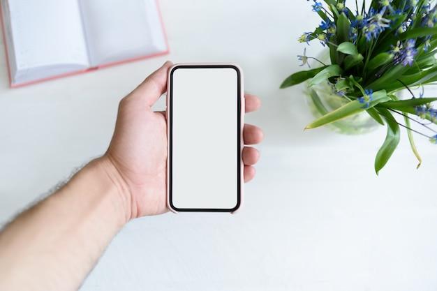 Mão masculina com um smartphone. tela em branco branca. mesa com caderno e flores em