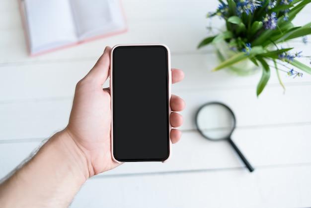 Mão masculina com um smartphone. tela em branco preta. mesa com caderno e flores em