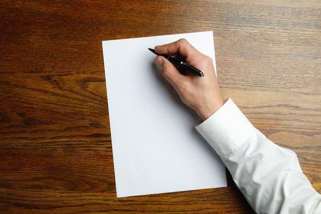 Mão masculina com uma caneta e escrevendo na folha vazia na mesa de madeira.